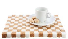 Tazza di caffè vuota su un piattino con tre pezzi dello zucchero bruno sulla a Immagini Stock Libere da Diritti