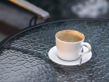 Tazza di caffè vuota sulla tavola di vetro, mattina Fotografia Stock