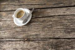 Tazza di caffè piena a metà con il cucchiaio sulla tavola di legno Immagine Stock