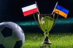 Tazza di calcio e bandiere dell'Ucraina e del polacco Fotografia Stock Libera da Diritti