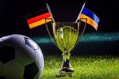 Tazza di calcio e bandiere dell'Ucraina e del tedesco Fotografia Stock Libera da Diritti