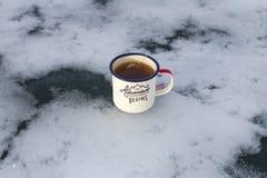 Tazza di campeggio Enameled del viaggiatore con il tè caldo della lavanda e della bustina di tè sul bello ghiaccio scenico sotto  Fotografia Stock