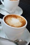 Tazza di cappuccino caldo sui precedenti neri Fotografie Stock