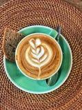 Tazza di cappuccino con arte ed il pane del caffè immagini stock libere da diritti