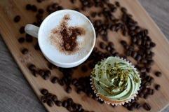 Tazza di cappuccino con i chicchi di caffè e del bigné Fotografia Stock