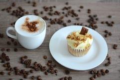 Tazza di cappuccino con il bigné Fotografie Stock