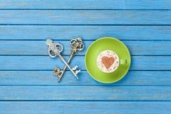Tazza di cappuccino con il simbolo di forma del cuore e due chiavi Fotografia Stock