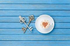 Tazza di cappuccino con il simbolo di forma del cuore e due chiavi Immagine Stock
