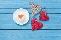 Tazza di cappuccino con il simbolo ed i giocattoli di forma del cuore Fotografia Stock