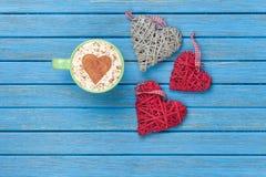 Tazza di cappuccino con il simbolo ed i giocattoli di forma del cuore Immagini Stock