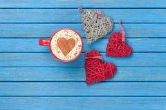 Tazza di cappuccino con il simbolo ed i giocattoli di forma del cuore Fotografie Stock