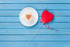 Tazza di cappuccino con il simbolo ed il giocattolo di forma del cuore Fotografie Stock