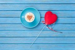 Tazza di cappuccino con il simbolo ed il giocattolo di forma del cuore Immagini Stock