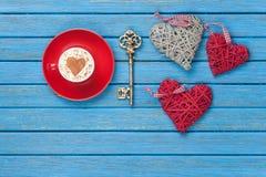 Tazza di cappuccino con il simbolo, la chiave ed i giocattoli di forma del cuore Fotografie Stock Libere da Diritti