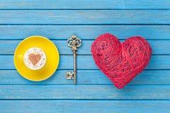 Tazza di cappuccino con il simbolo, la chiave ed il giocattolo di forma del cuore Fotografia Stock Libera da Diritti