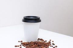 Tazza di carta con caffè a casa sulla tavola Fotografia Stock