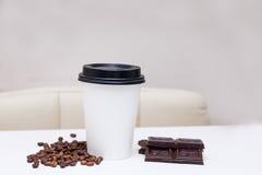 Tazza di carta con di pepita di cioccolato e i beens del caffè Fotografia Stock Libera da Diritti