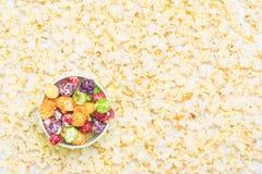 tazza di carta con il popcorn multicolore del caramello contro lo sfondo di popcorn pronto fotografia stock libera da diritti