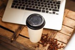 Tazza di carta del caffè con il taccuino del computer su un fondo di legno Immagini Stock