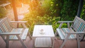 Tazza di CCoffee con illuminazione sul fondo di legno Fotografia Stock