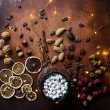 Tazza di cioccolata calda o di cacao tradizionale con la caramella gommosa e molle, la cannella, i dadi e le spezie sulla tavola  Fotografie Stock