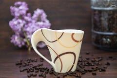 Tazza di Coffe con i chicchi di caffè e contenitore di diffusione del caffè e fiore lilla fotografia stock