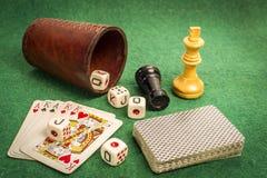 Tazza di dadi con le carte ed i pezzi degli scacchi della piattaforma Fotografia Stock