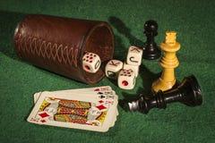 Tazza di dadi con le carte ed i pezzi degli scacchi della piattaforma Fotografie Stock