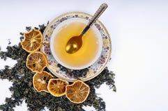 Tazza di erbe di tè con i fogli ed i limoni Fotografia Stock