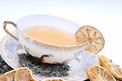 Tazza di erbe di tè con i fogli ed i limoni Fotografie Stock