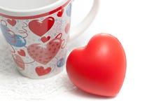 Tazza di giorno dei biglietti di S. Valentino e cuore rosso su bianco Immagine Stock