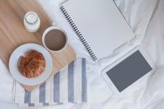 tazza di latte, del croissant e del libro caldi sulla tavola di funzionamento di mattina Fotografia Stock