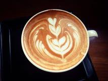 Tazza di latte o di cappuccino caldo con arte affascinante del latte Fotografia Stock