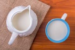 Tazza di latte sulla tavola con il panno e la brocca di juta Fotografie Stock