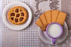 Tazza di latte sulla tavola con il panno e una crostata del cioccolato Fotografie Stock Libere da Diritti