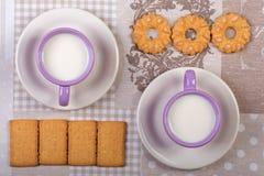 Tazza di latte sulla tavola con il panno ed i biscotti Fotografia Stock Libera da Diritti