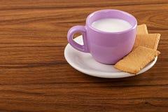 Tazza di latte sulla tavola di legno con i biscotti Immagine Stock