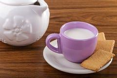 Tazza di latte sulla tavola e sulla brocca con i biscotti Fotografia Stock