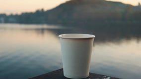 Tazza di Libro Bianco con i supporti caldi del caffè sull'inferriata sopra l'acqua al tramonto stock footage
