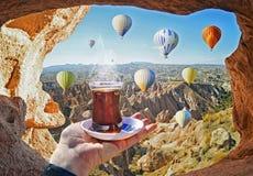 Tazza di mattina di tè con la vista delle mongolfiere variopinte Immagini Stock