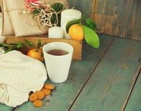 Tazza di Natale di tè con i biscotti, i regali, le candele ed i mandarini Fotografie Stock