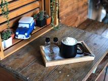 Tazza di panna di raggiro del caffè espresso in bianco e nero sulla tavola di legno con luce naturale immagine stock