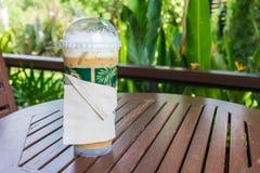 tazza di plastica del cappuccino del ghiaccio sulla tavola di legno Fotografie Stock