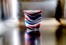 Tazza di plastica rossa, bianca e blu che getta le ombre in un lavandino immagini stock libere da diritti