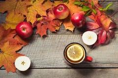 Tazza di riscaldamento di tè, decorazione delle foglie di autunno, mele sul bordo di legno Di caduta vita ancora Vista superiore Immagine Stock