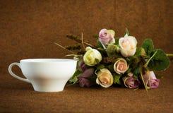 Tazza di tè bianca accanto dalle rose Fotografia Stock