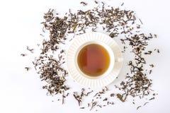 Tazza di tè bianca con tè e la foglia di tè Immagine Stock