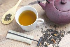 Tazza di tè bianca della porcellana, teiera del ghisa con il cucchiaio di legno e fotografie stock