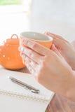 Tazza di tè calda della tenuta della mano Immagini Stock Libere da Diritti