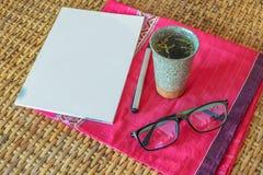 Tazza di tè calda sulla mobilia del rattan, cima della tavola, leggente tempo Fotografie Stock